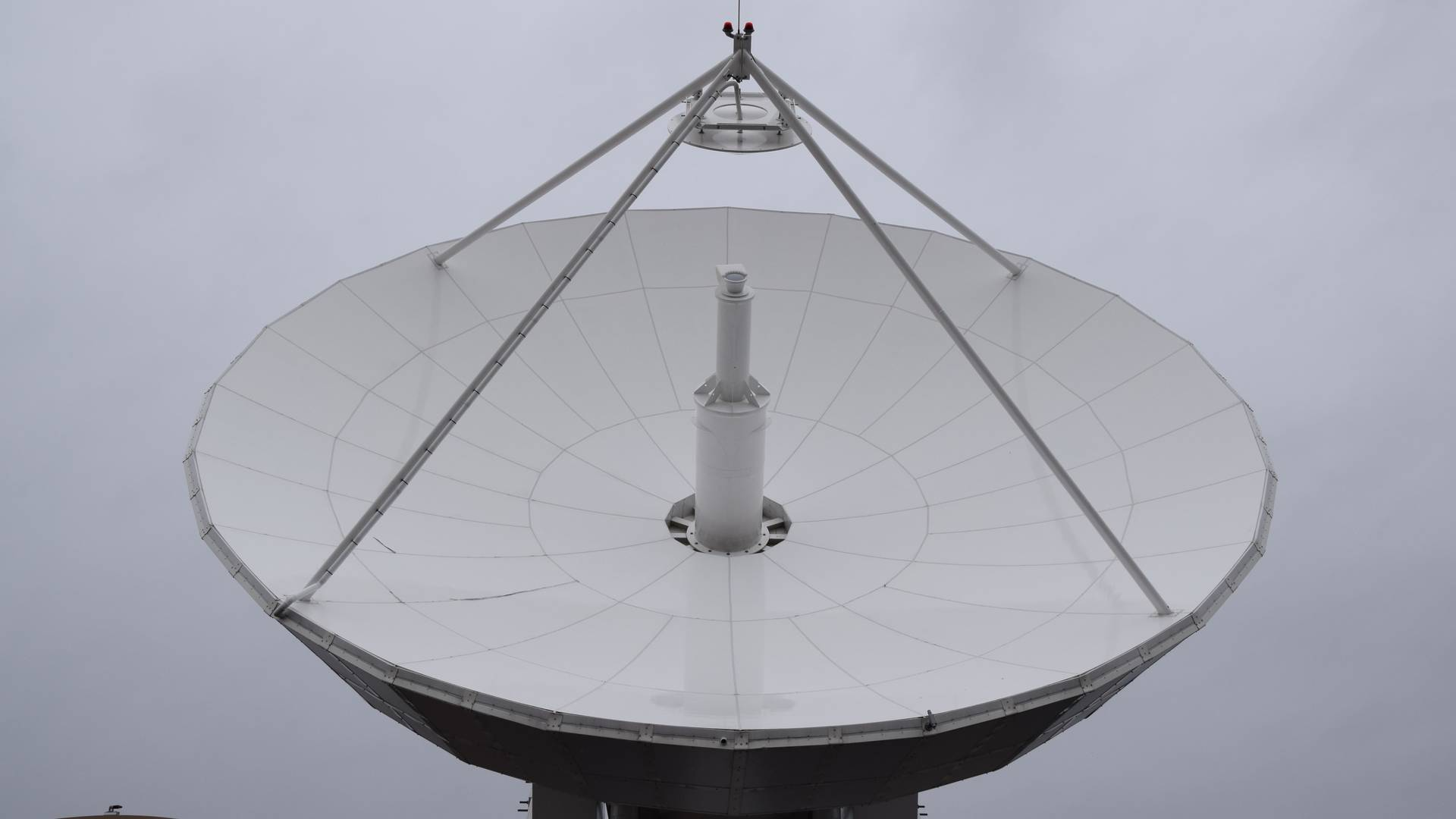 White ground satellite pointed toward cloudy sky